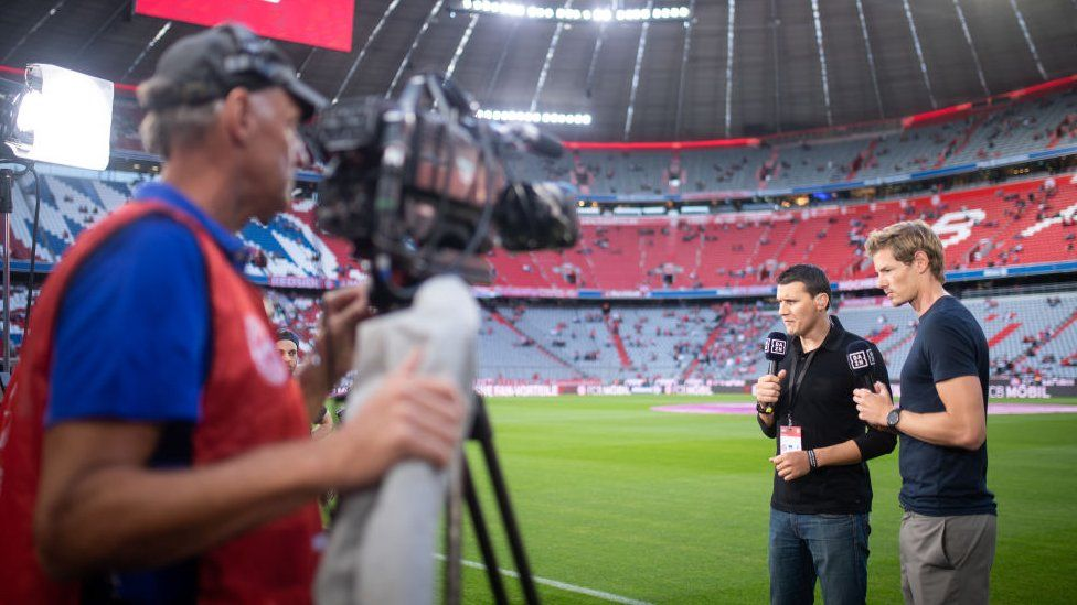 A cameraman films presenters on the side of Bayern Munich's pitch