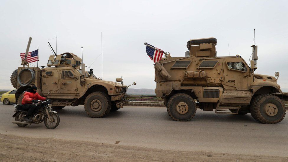 A US military vehicle tows another vehicle on the outskirts of the Syrian city of Qamishli on 12 February 2020