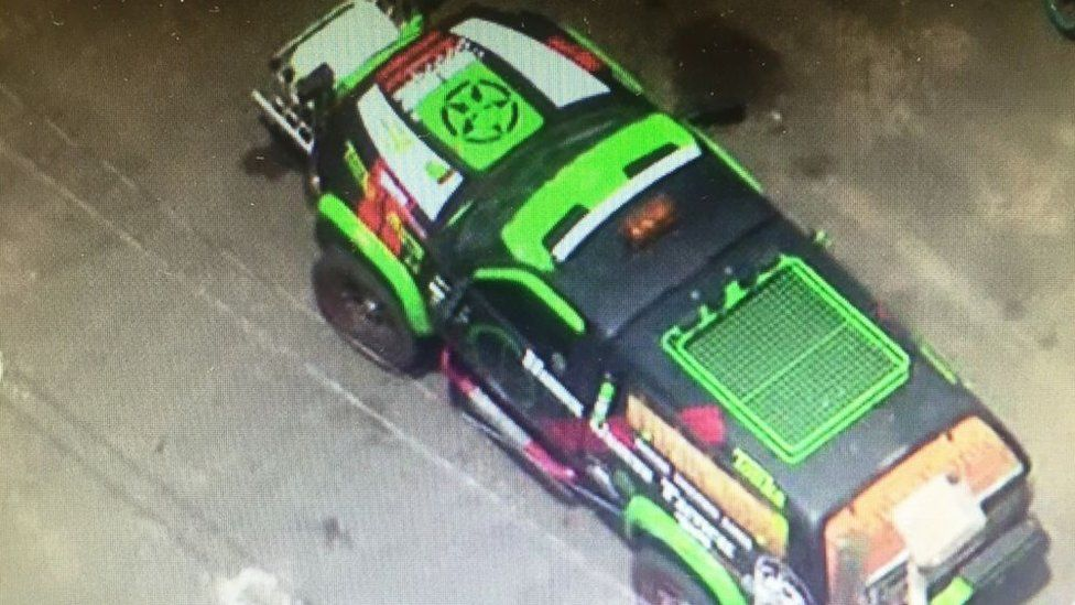 The modified truck, which is decorated in neon green, sits in a police impound lot