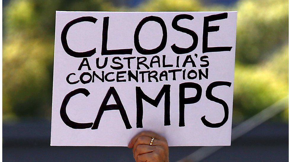 A placard reading 'close Australia's concentration camps' is held up during a rally in support of refugees in central Sydney