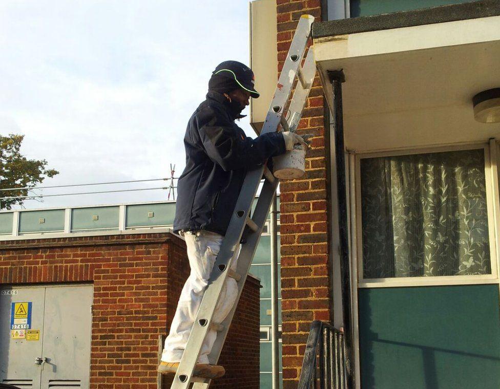 Julie Stennett up a ladder painting
