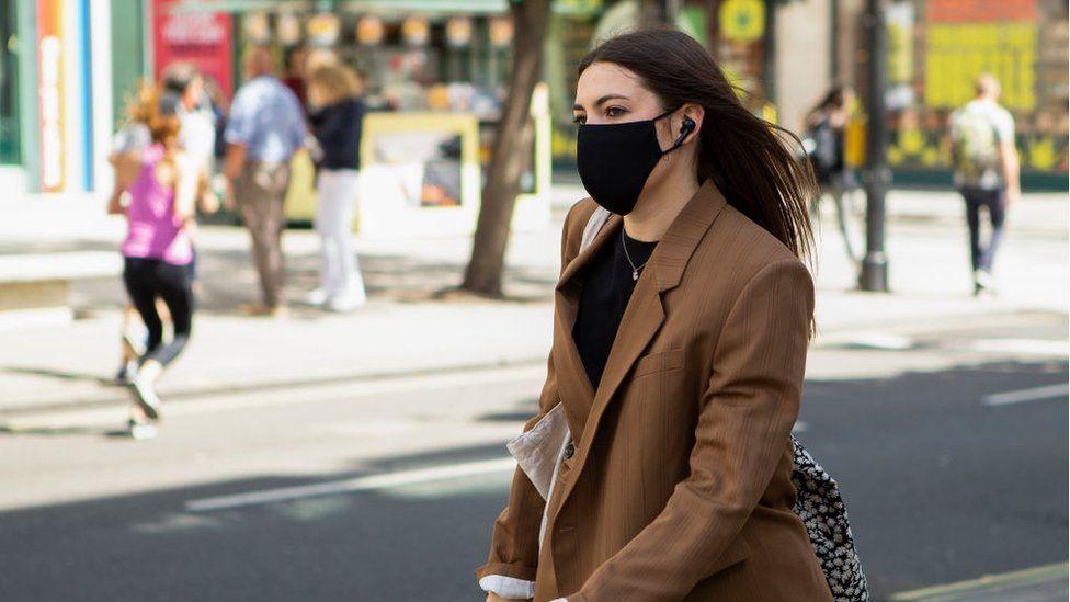 A woman wearing a mask walks down Oxford Street