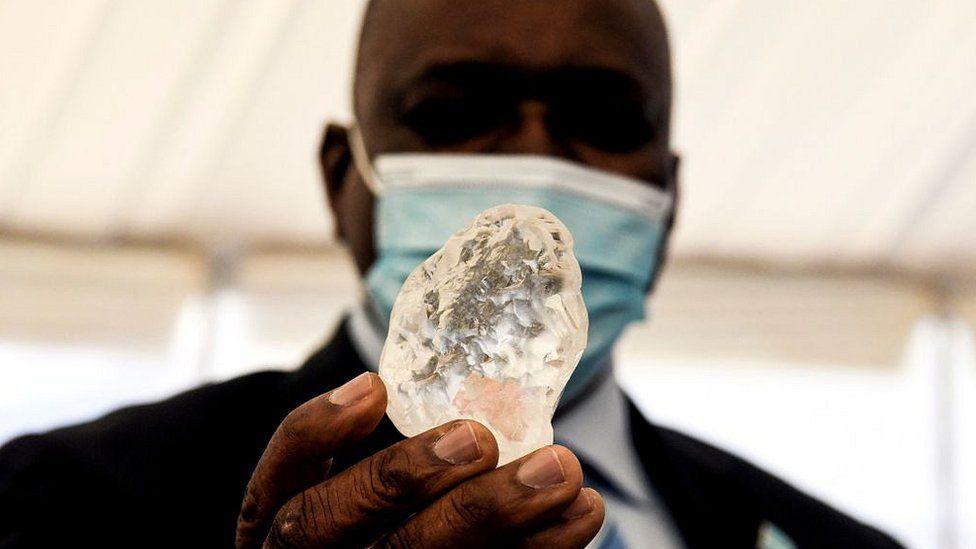 Botswana President Mokgweetsi Masisi holds the diamond in Gaborone, on June 16, 2021