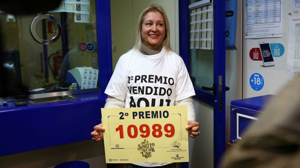 A worker of a lottery office in Madrid celebrates selling the number 10989 that got the second prize in the lottery draw in Madrid.