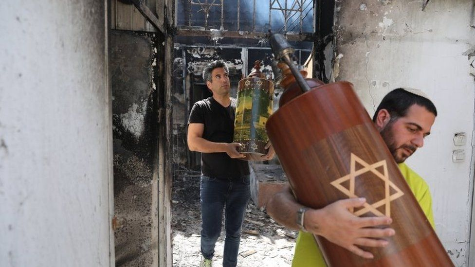 Men take out a Torah scroll from a burned synagogue in Lod, Israel (12 May 2021)