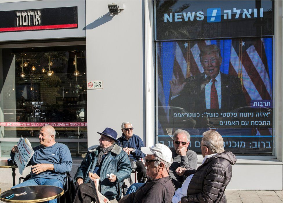 Israelis sit outside cafe in front of screen showing Donald Trump