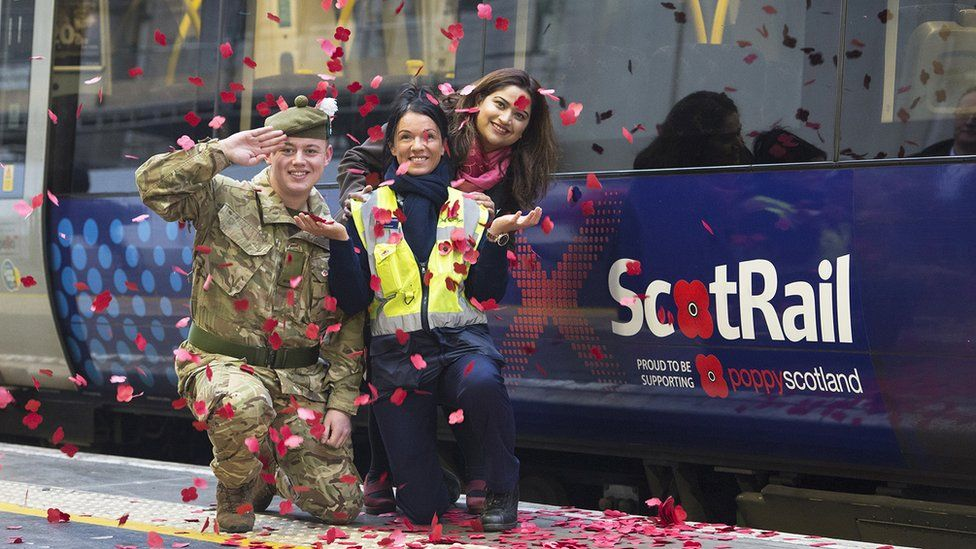 three people pose by a poppy logo on a train