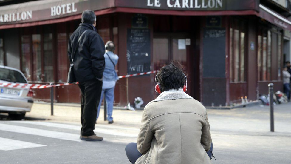 A woman sits outside of the Carillon bar in the 10th district of Paris on November 14, 2015,