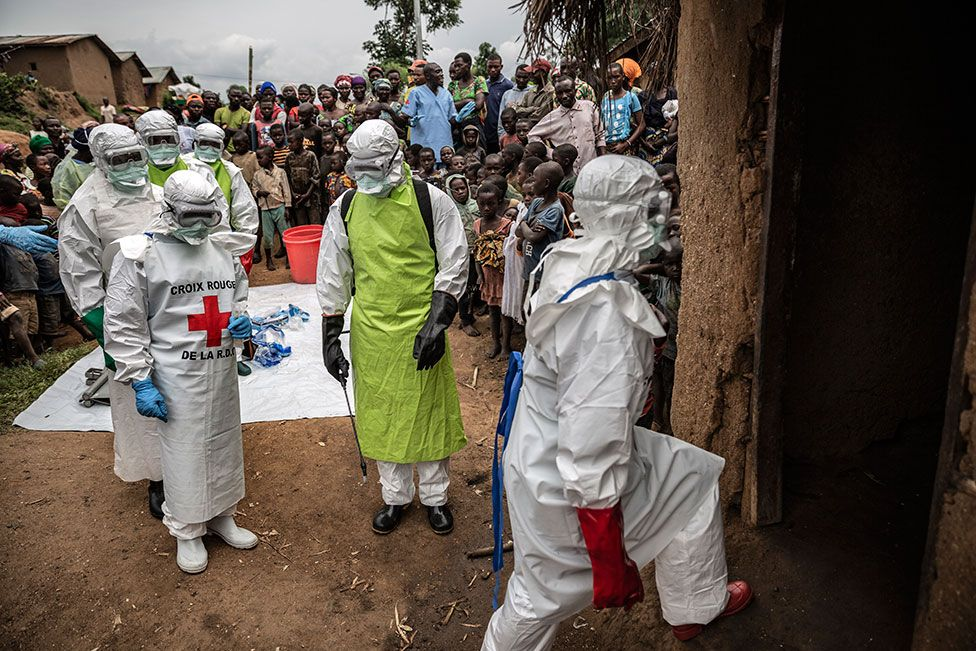 Neighbours and Red Cross burial workers in protective clothing gather outside a home