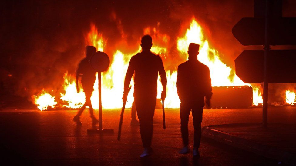 Lebanese protesters walk past burning tyres in the southern town of Sidon on 17 December 2019