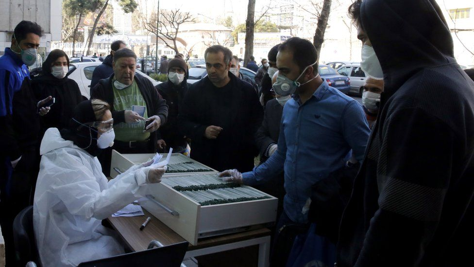 A health worker registers people waiting for a Covid-19 test outside a lab in Tehran, Iran (9 March 2020)