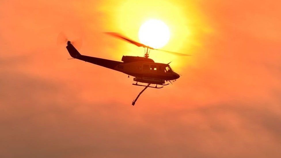 A helicopter prepares to drop water on a large bushfire in Bargo, 150km southwest of Sydney