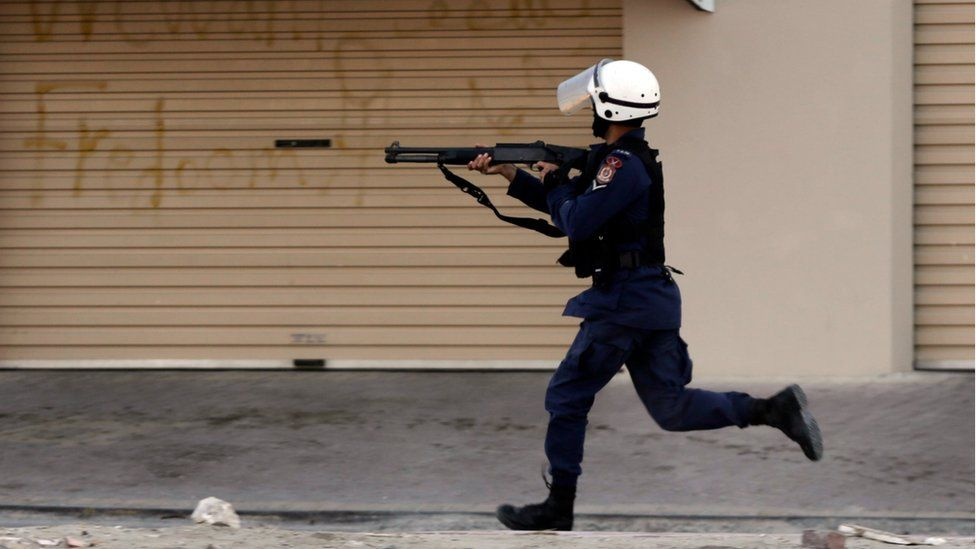Riot policeman fires birdshot towards an anti-government protester who was throwing a steel bar toward police, during clashes in Musalla