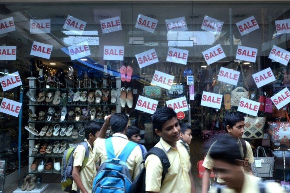 Indian schoolchildren stand in front of a store window offering discounts in Mumbai on August 3, 2016