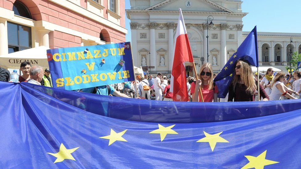 Young people wave Polish and European Union flags during the yearly Schumann Parade supporting EU ideas, in Warsaw, Poland, Saturday, May 7, 2016.