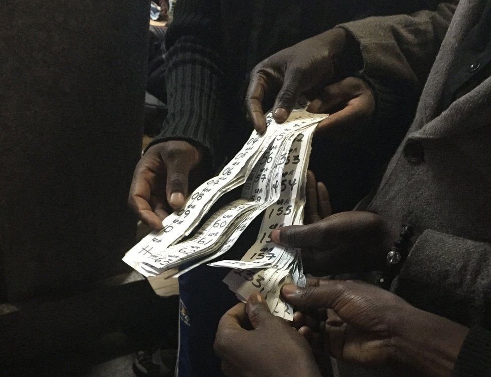 Men distribute numbers to depositors who want to withdraw their money