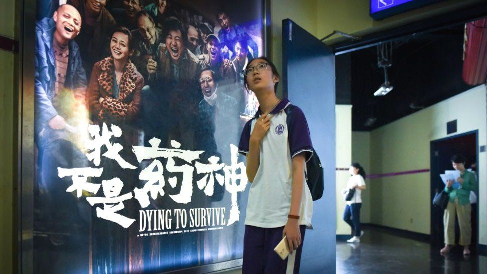 In this picture taken on July 12, 2018, a girl walks past a poster of the film 'Dying to Survive' at a cinema in Beijing