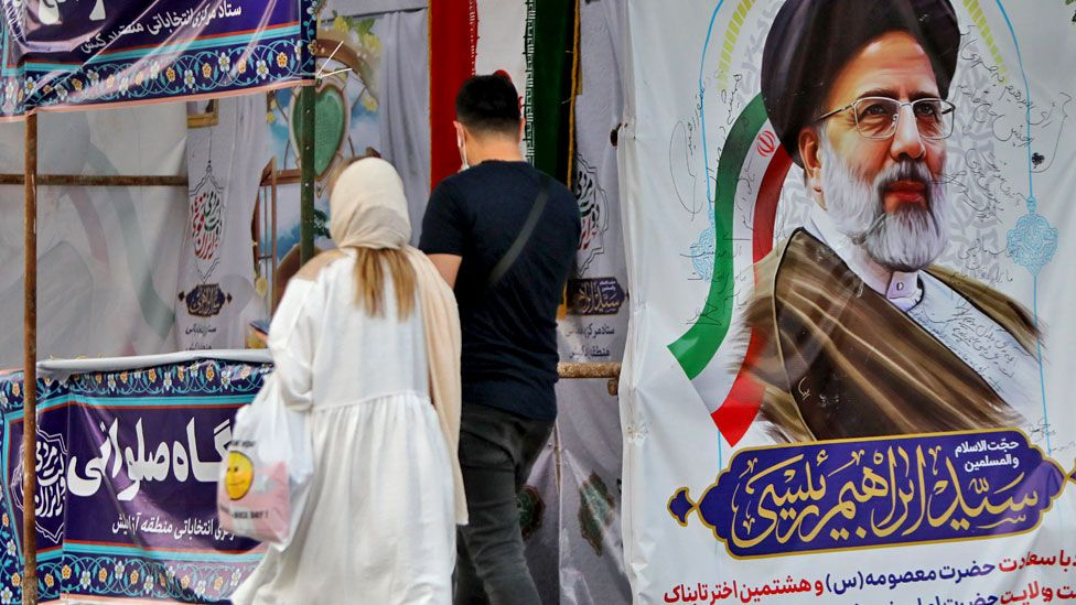 People walk past a poster of Ebrahim Raisi during the Iranian presidential election on Iran's Kish Island (18 June 2021)
