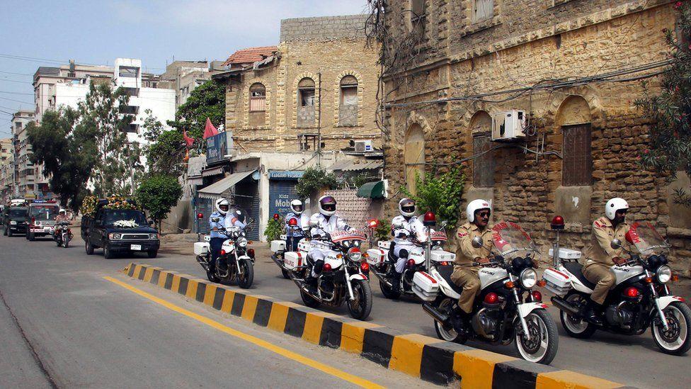 Pakistani military soldiers on motorbikes transport the coffin through Karachi, Pakistan