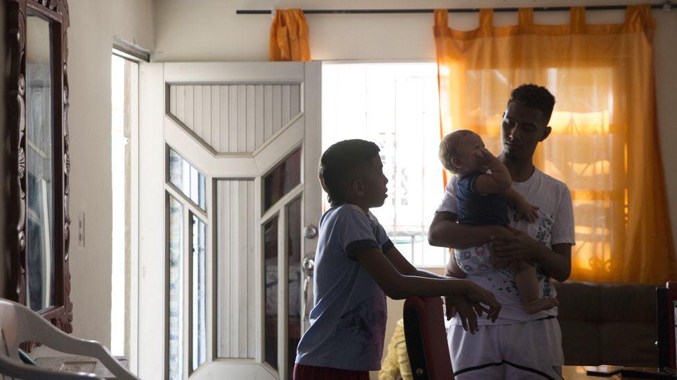 El esposo y el hijo del líder de la liga, Eidavis Montes, cuidan a su bebé en la sala de su casa.