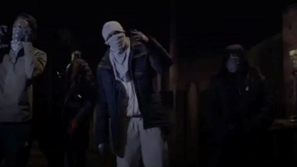 Men wearing facemasks rapping in a drill video