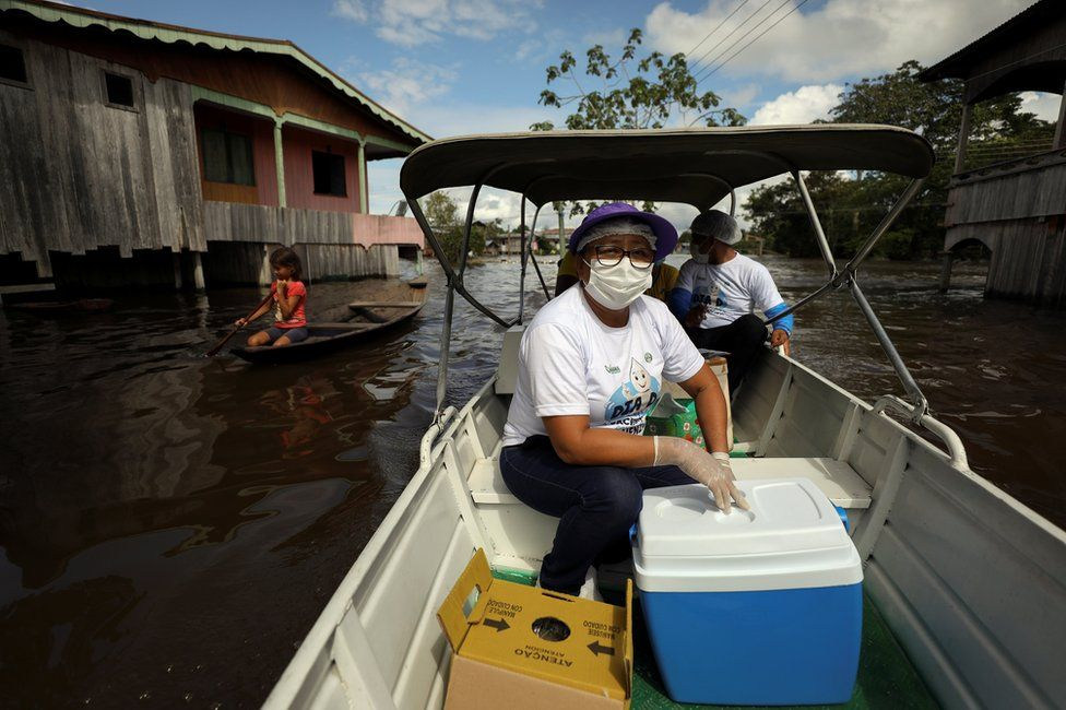 Municipal health worker Neuda Sousa is seen in a boat with a box of the Oxford/AstraZeneca vaccine against the coronavirus disease on a street a flooded by the rising Solimoes river
