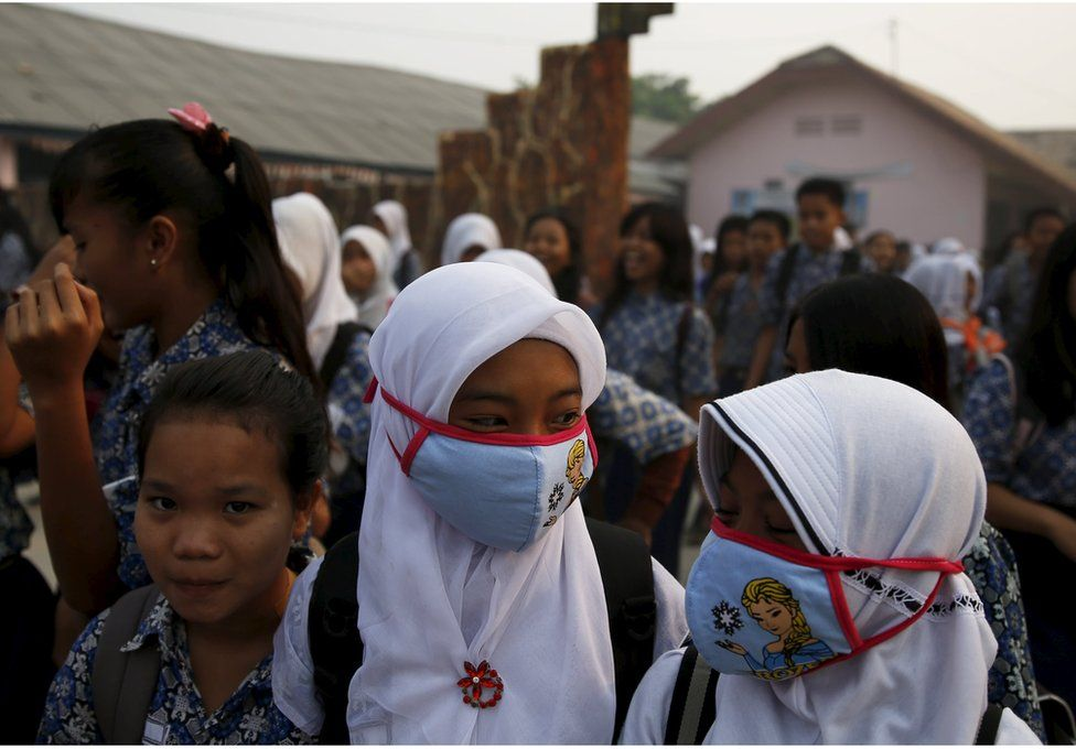 Students, wearing face masks, walk in front of their school as they prepare to head home due to the unhealthy quality of air in Palembang, on Indonesia's Sumatra island, 10 September 2015.