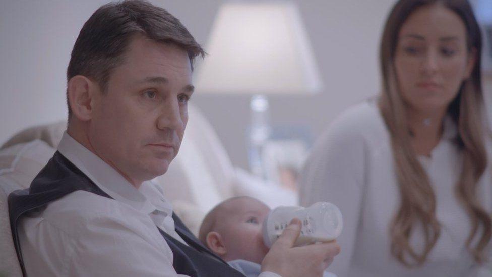 Kevin Lane bottle feeding his baby boy