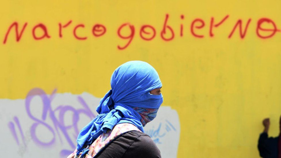 """A student of the National Autonomous University of Honduras (UNAH) takes part in a protest near a wall reading """"Narco-government"""" in Tegucigalpa on 14 August 2019"""