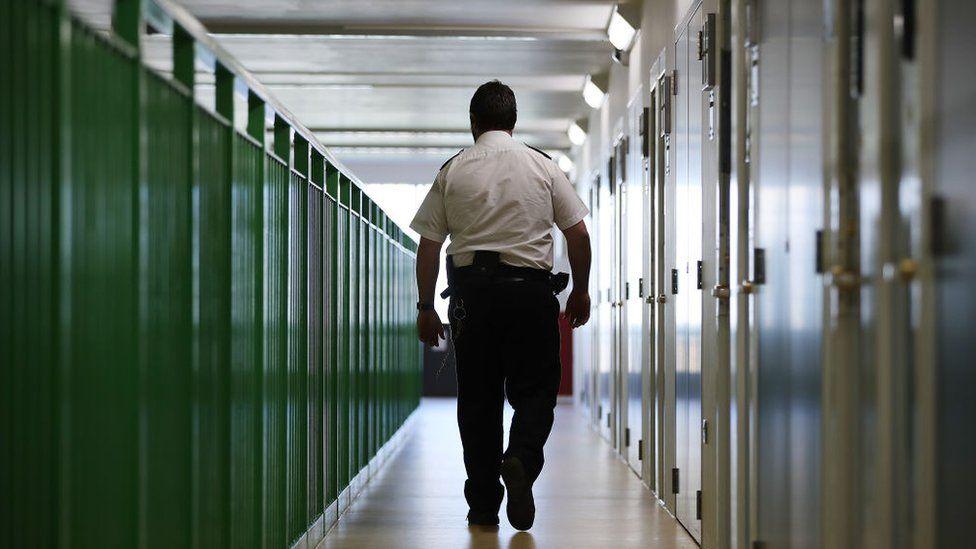 Prison officer walks past cell doors at HMP Berwyn, Wrexham