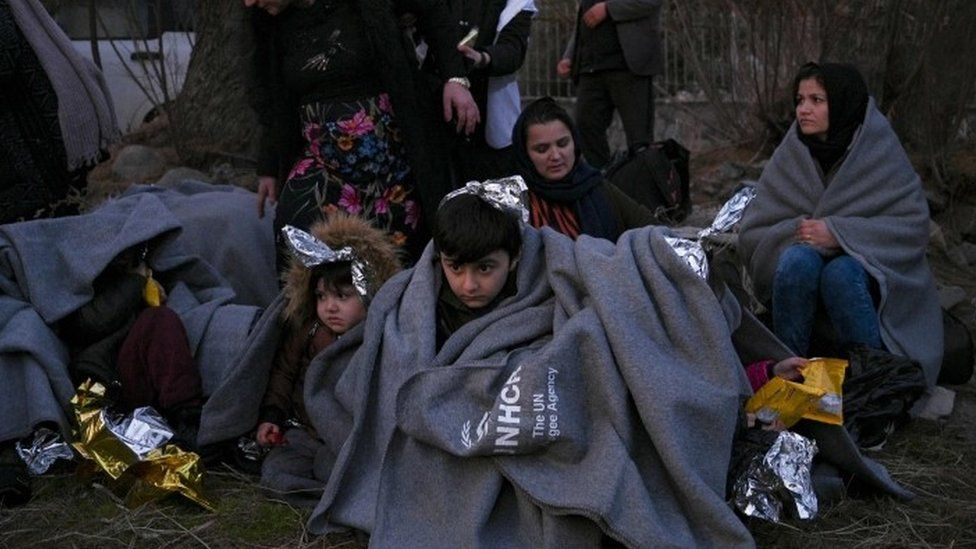 Migrants sit on a beach covered with blankets on the Greek island of Lesbos