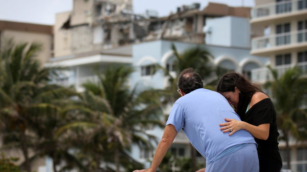 A couple at the beach reacts near the partially collapsed residential building as the emergency crews continue search and rescue operations for survivors, in Surfside, near Miami Beach, Florida, U.S. June 26, 2021