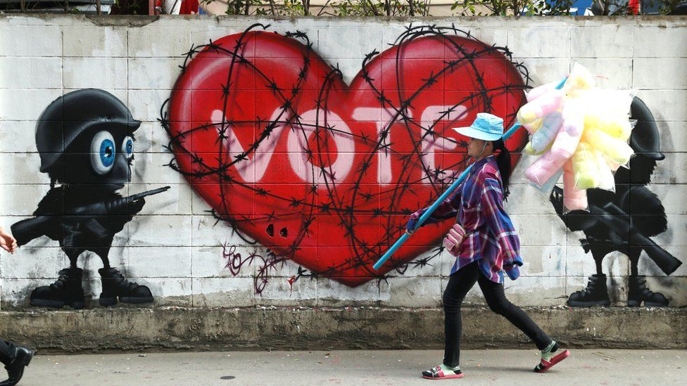 """Woman walking past a """"Vote"""" graffiti"""