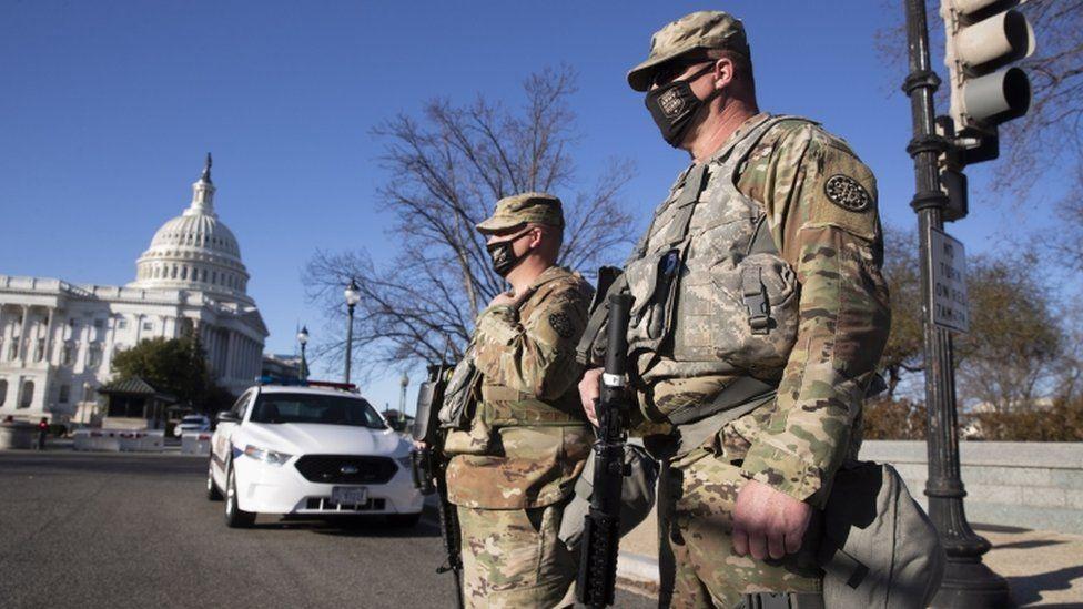 สมาชิกของกองกำลังพิทักษ์ชาติยืนอยู่ที่แนวรบด้านตะวันออกของศาลาว่าการสหรัฐฯในวอชิงตันดีซี