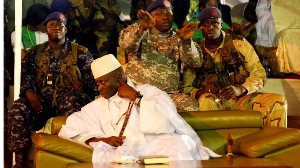 Gambia's President Yahya Jammeh sits on a sofa surrounded by military men at a rally in Banjul, Gambia on 29 November 2016