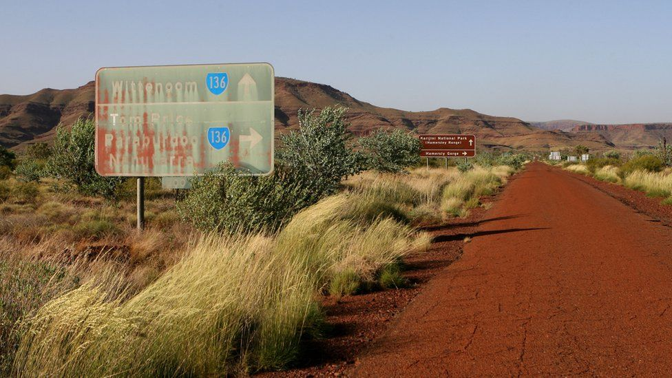 A faded road sign pointing to Wittenoom, and to other towns in the Pilbara area