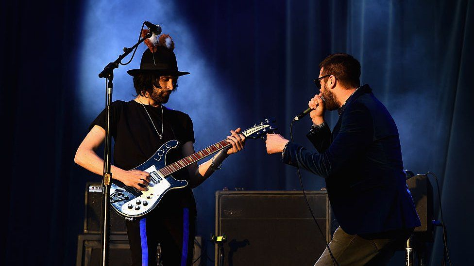 Kasabian performing on stage