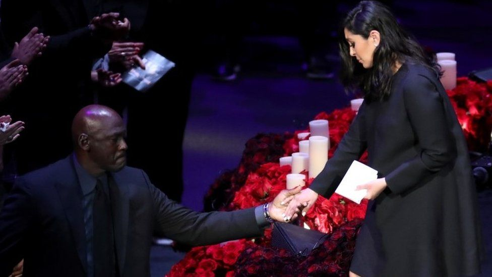 Former basketball player Michael Jordan helps Vanessa Bryant get off the stage during a public memorial for her late husband