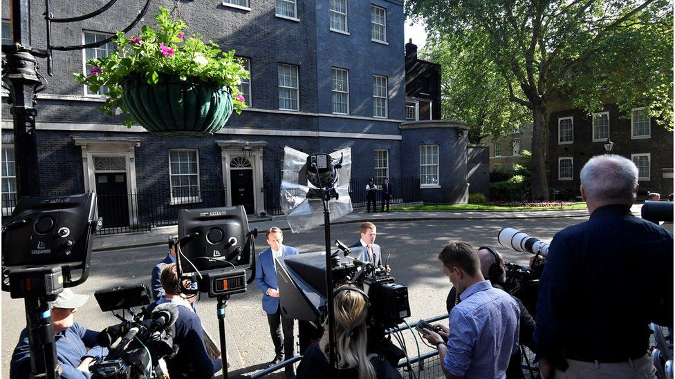 Members of the media wait outside of Downing Street