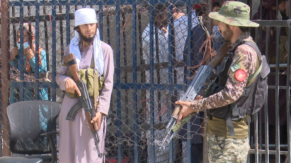 An armed Taliban fighter (left) and an armed Pakistani soldier at the Torkham crossing on the Pakistani-Afghan border