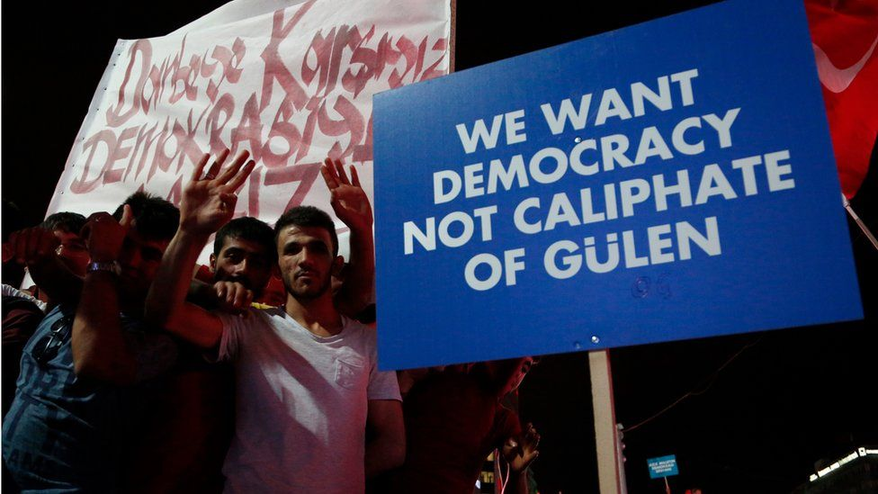 Supporters of Turkish President Recep Tayyip Erdogan hold a placard
