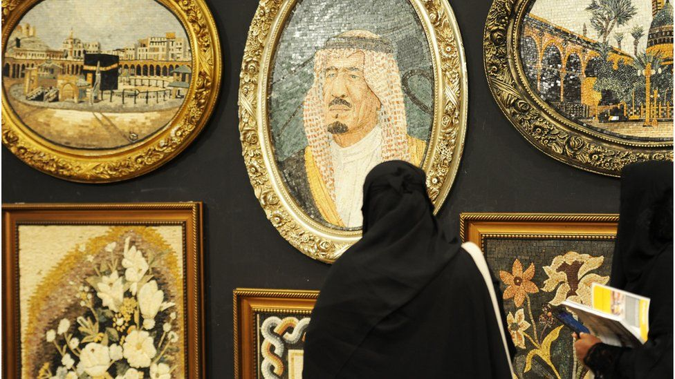 A Saudi woman looks at a portrait of the Saudi King during an interior design fair in the Red Sea city of Jeddah, 8 November 2017