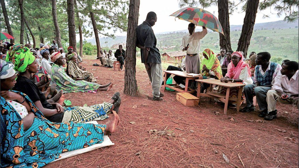 A picture taken 03 December 2003 shows a witness facing the president (with umbrella) of a gacaca court session in Rukira, during a hearing in relation with the 1994 Rwandan genocide