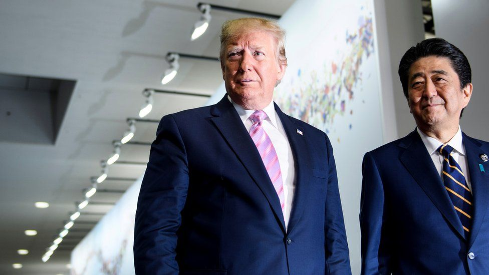 Japan's Prime Minister Shinzo Abe (R) greets US President Donald Trump as he arrives for the G20 Summit in Osaka on June 28, 2019