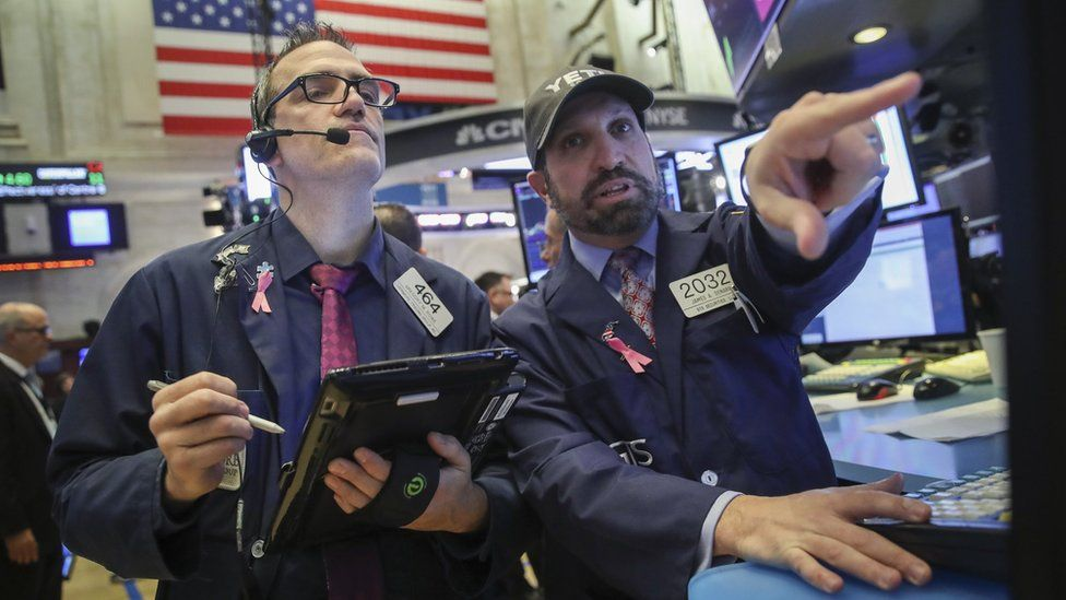 Traders and financial professionals work on the floor of the New York Stock Exchange (NYSE) at the opening bell, October 25, 2018 in New York City