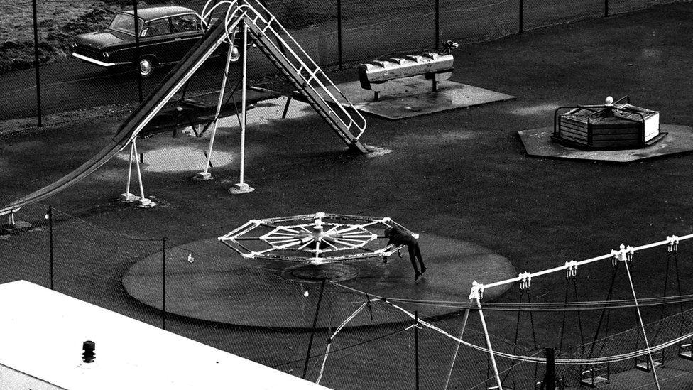 Bachgen yn chwarae ar ei ben ei hun mewn maes chwarae yn Aberfan rhai wythnosau wedi'r gyflafan // A generation wiped out: American photographer Chuck Rapoport took this photo of a lonely young boy on a merry-go-round in Aberfan weeks after the disaster