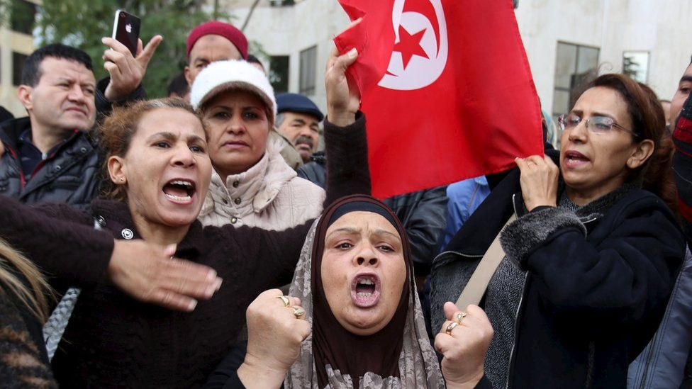 People shout slogans at a protest to condemn a suicide bomb attack in Tunis