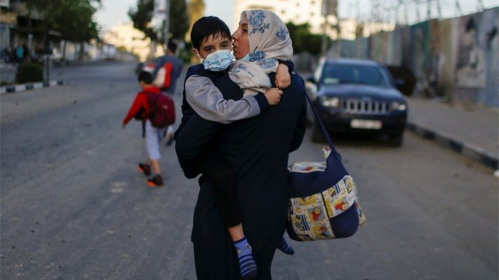 A Palestinian woman carrying her son evacuates after their tower building was hit by Israeli airstrikes, amid a flare-up of Israeli-Palestinian violence, in Gaza City May 12, 2021.