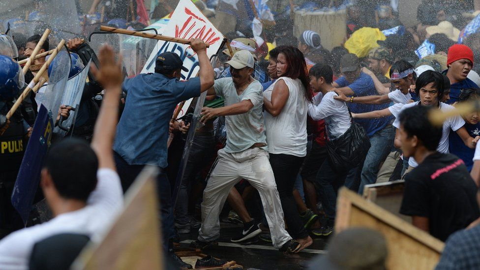 Philippine police (L) fire water cannon as they clash with protesters in Manila