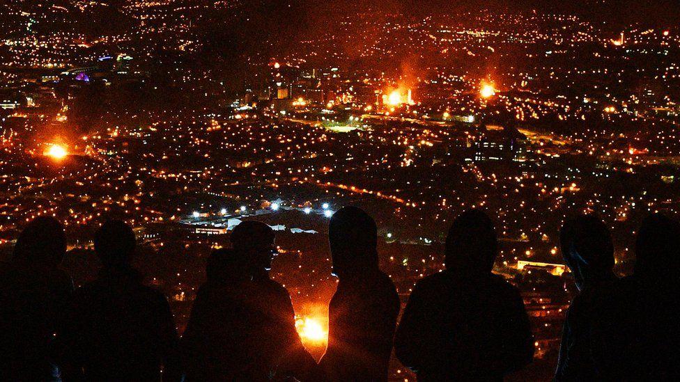 People watch bonfires across Belfast from the top of Black Mountain